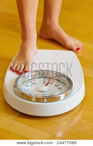 feet of a woman on bathroom scales