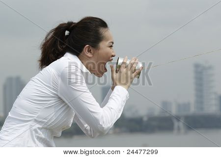 Asian Business Woman Shouting Into A Tin Can Phone.