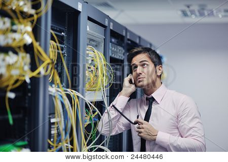 young business man computer science engeneer talking by cellphone at network datacenter server room asking  for help and fast solutions and services