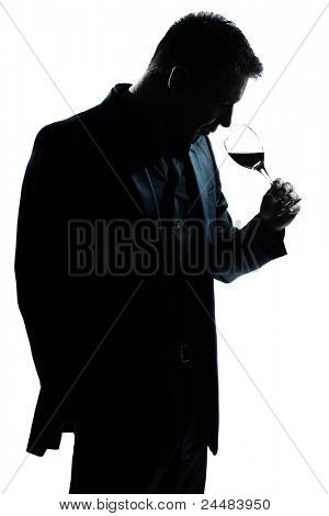 one caucasian man portrait silhouette smelling red wine glass in studio isolated white background