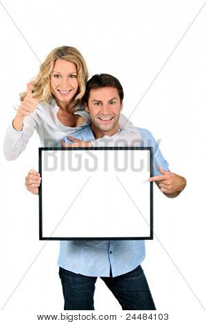 Excited couple pointing to a blank sign