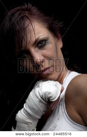 young female fighter on black background