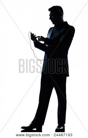 one caucasian man text messaging telephone listening to music full length silhouette in studio isolated white background