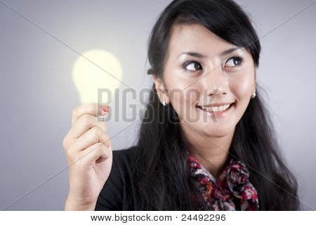Pretty Business Woman Holds A Light Bulb