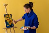 Girl Artist Paints Sunflowers Oil Paints On Canvas. She Is Wearing Blue Sweater. Woman Is Holding Br poster