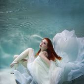 Underwater Girl. Beautiful Red-haired Woman In A White Dress, Swimming Under Water. Nymph Or Mermaid poster