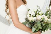 Beautiful Bride In White Dress Holding Lush Wedding Bouquet Of Roses And Eucalyptus Greenery Indoors poster