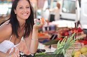 picture of bartering  - Brunette buying fruit and vegetables at local market - JPG