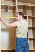 pic of assemblage  - The man is engaged in assemblage of a new wardrobe - JPG
