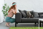 Smiling Young Woman Looking At Her Tabby Cat While He Sitting On Couch At Home poster