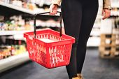 Woman Holding Shopping Basket And Walking In Grocery Store Aisle. Lady Buying Groceries And Food In  poster