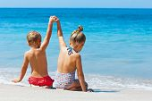Happy Kids Have Fun In Sea Surf On White Sand Beach. Couple Of Children Sit In Water Pool With Hands poster