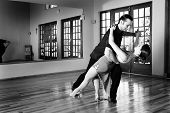 picture of ballroom dancing  - A young adult couple dancing and practicing ballroom together in a studio  - JPG