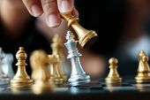 Close Up Shot Hand Of Business Woman Moving Golden Chess To Defeat And Kill Silver King Chess On Whi poster