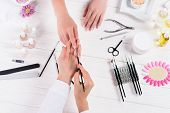 Cropped Image Of Beautician Doing Manicure To Woman At Table With Nail Polishes, Nail Files, Nail Cl poster