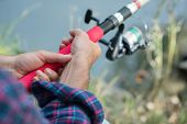 Man fishing at river bank, summer outdoor. Summer leisure, hobby. Fishing. Angling. Mans hand with  poster
