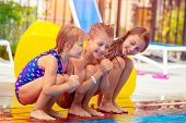 Three happy kids sitting near the pool, having fun in aqua park, best friends with pleasure spending poster