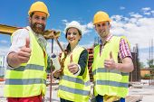 Portrait of three cheerful colleagues in a construction team looking at camera, while showing thumbs poster