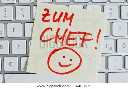 a memo is on the keyboard of a computer as a reminder: for chief