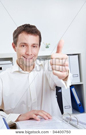 Smiling business manager holding his thumb up in the office