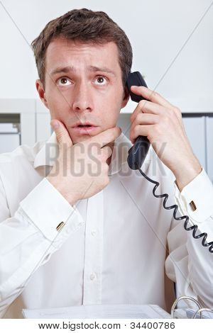 Business man at desk in office thinking on phone