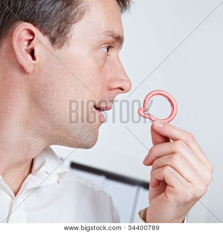 Business man holding speech balloon symbol near his mouth