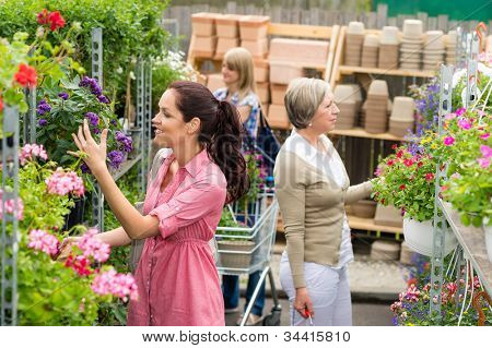 Woman taking potted flower shopping purple plant in garden center