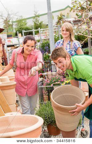 Male worker at garden center help customer choose flower pot
