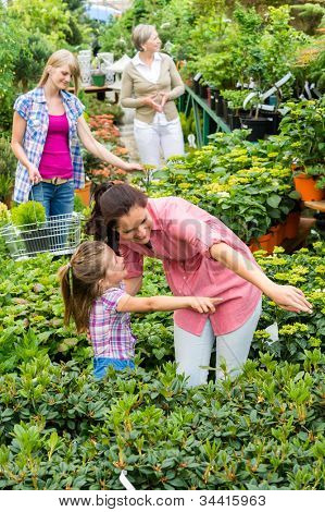 Mother and daughter choosing house plants at garden centre shop