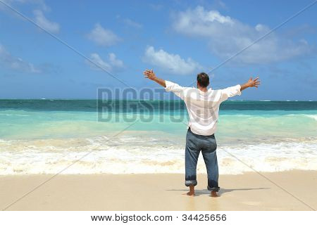 Single Male Standing On Beach Facing Ocean Open Arms