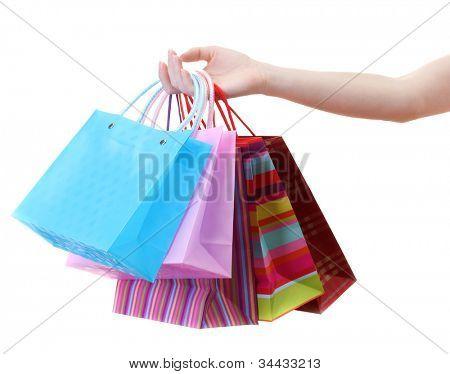 Weibliche Hand halten helle Einkaufstaschen, isolated on white