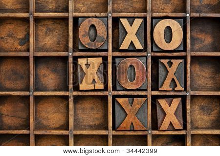 tic-tac-toe or noughts and crosses game - vintage letterpress printing block X and O in wooden grunge typesetter box with dividers