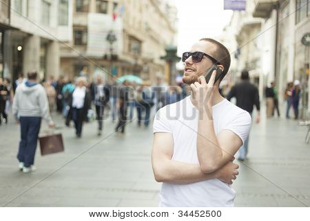 Young Man With Sunglasses And Phone Walking On Street