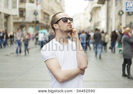 Young Man With Sunglasses And Cell Phone Walking