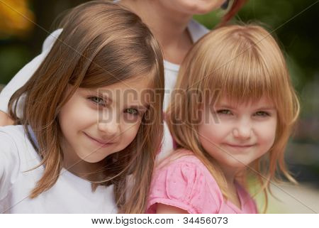 Cute Little Girls With Their Mom Outdoors