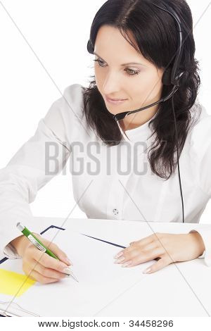 Portrait Of Brunette Call-center Customer's Support Operator With Headset  Writing A Document Isolat