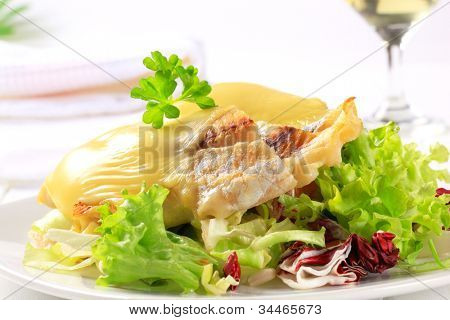 Fish fillet in cheese batter on lettuce on a white plate