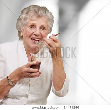 portrait of a senior woman eating a chocolate and cream cup indoor