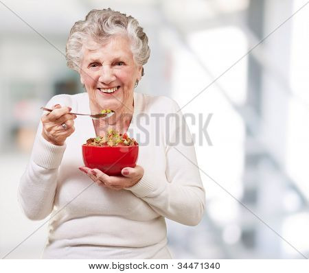 portrait of a senior woman holding a cereals bowl indoor