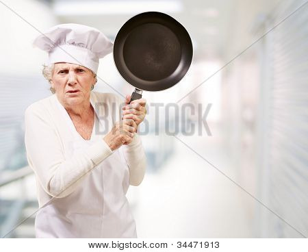 angry senior woman cook trying to hit with a pan at an entrance of a modern building