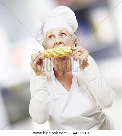 senior woman cook eating a corncob, indoor