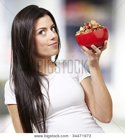 woman holding a delicious red breaksfast bowl against a street background