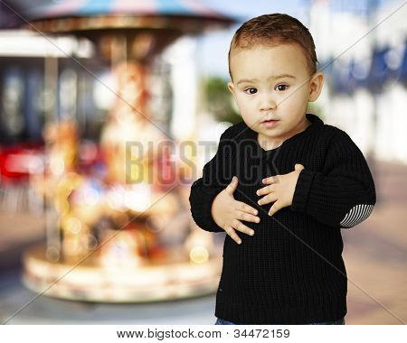 portrait of an adorable kid touching his stomach against a carousel