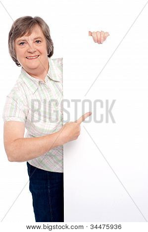 Causal Senior Lady Pointing Towards Placard