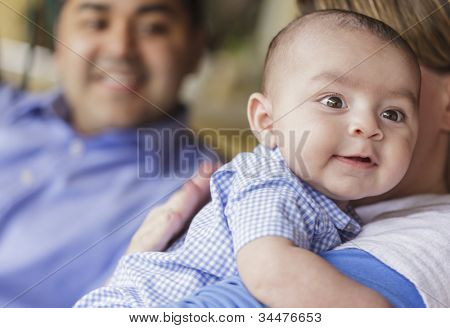Happy Attractive Mixed Race Couple Burping Their Smiling Son.