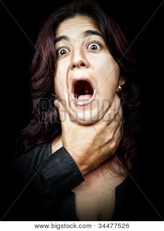 Dark portrait of a woman being abused and strangled by a man while she screams