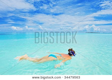 A woman in swimsuit snorkeling in Kuredu resort, Maldives island