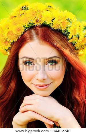 Portrait of a romantic young woman in a circlet of flowers outdoors.