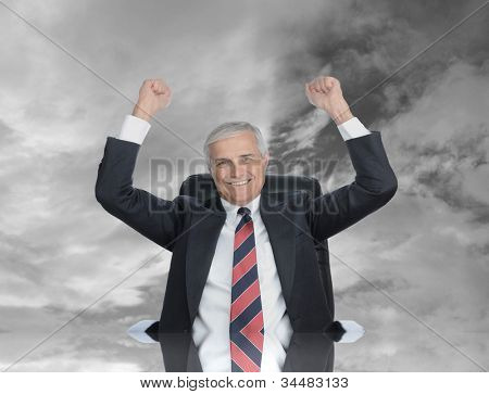 Businessman seated at his desk with his fists in the air to celebrating a closed deal. Sky Background with reflection in the desk top.
