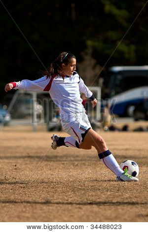 Female Soccer Player Swings Leg To Kick Ball